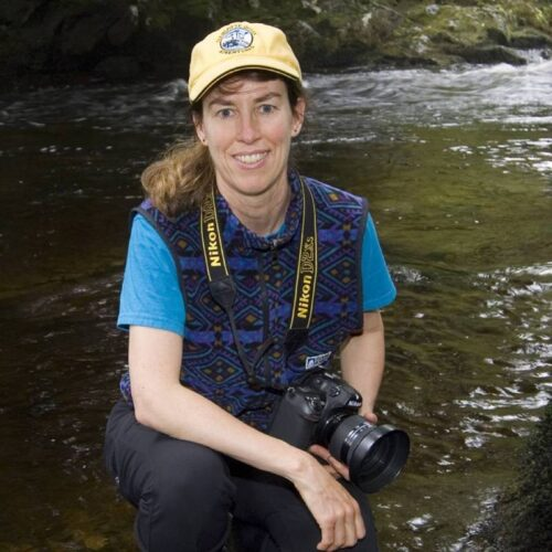 Amy Gulick kneeling in front of a river with a camera around her neck