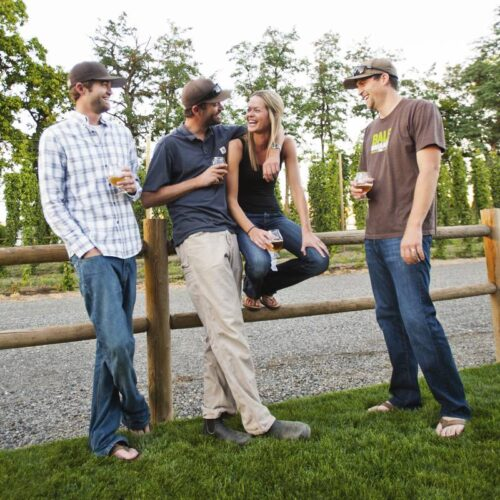 Four members of the Bale Breaker team leaning against a wood fence drinking a beer