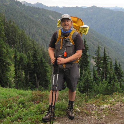 Bret Wirta with trekking poles and a backpack standing on a trail