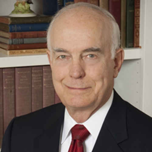 Daniel J. Evans wearing a black suit and red tie with books in the background