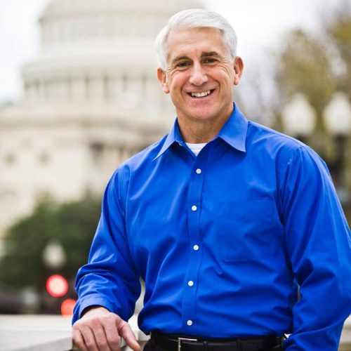 Dave Reichert wearing a blue button down shirt standing in front of the Washington State Capitol