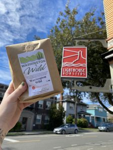 A bag of lighthouse roasters Washington Wild Blend is held up in front of the Lighthouse Roasters storefront