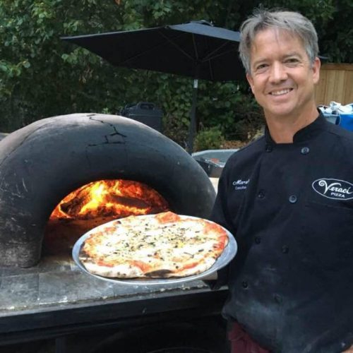 Marshall Jett holding a pizza in front of a wood pizza stove