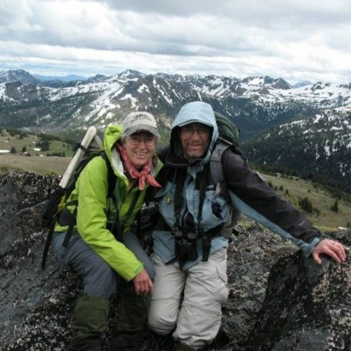 Tim Manns and Brenda Cunningham with backpacking gear and a mountain in the background