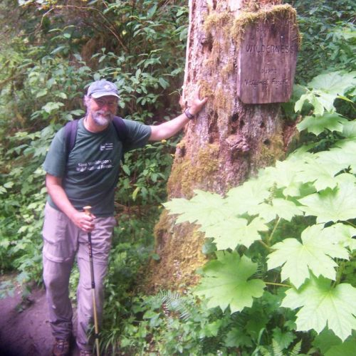 Tim McNulty leaning against a tree holding trekking pole