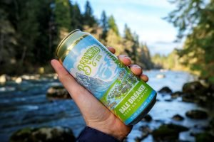 A can of Brewshed IPA held up in front of a free flowing river